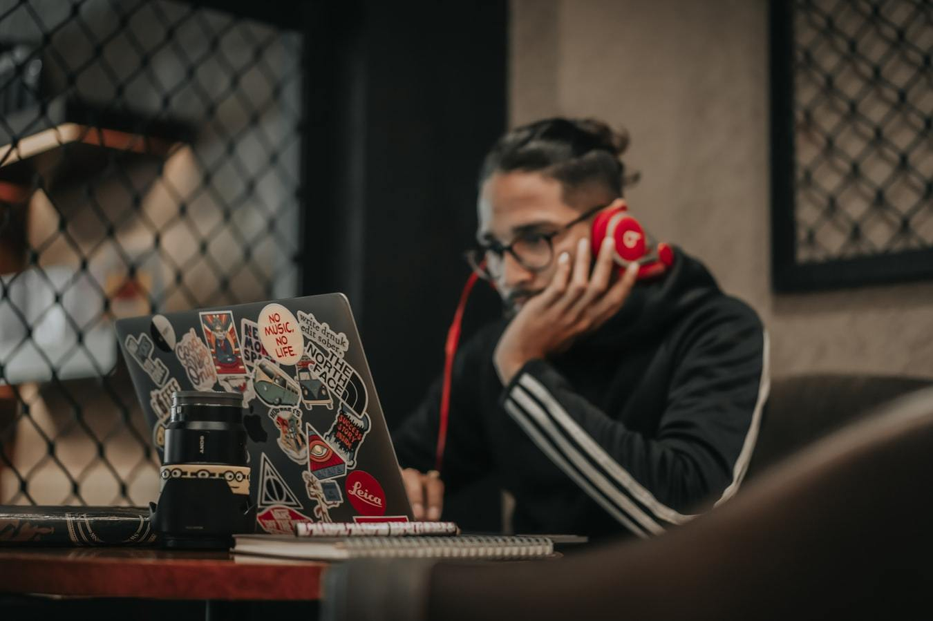 Person wearing a black hoody and red headphones works at a laptop with lots of arty stickers