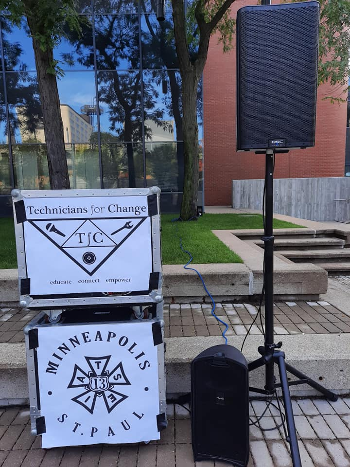 2 roadcases stacked next to a temporary sound system. The top one has a Technicians for Change logo, the lower one an IATSE Local 13 logo.