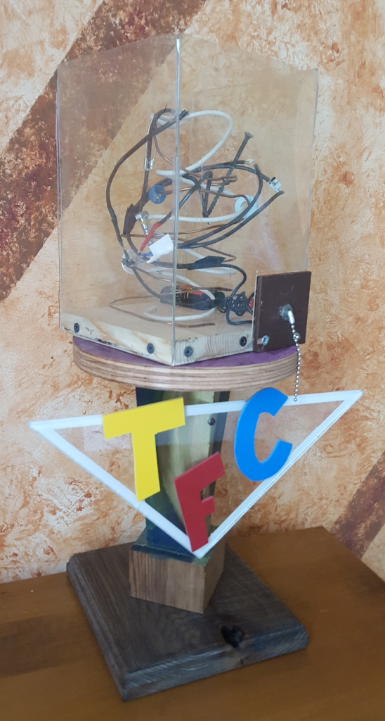 Wooden statuette with TFC-triangle logo and box with nest of electrical wiring, safety pins, and screws.